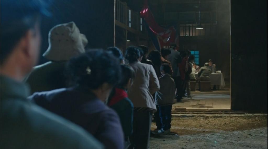 """Em """"Doctor Stranger"""", uma fila de pacientes espera para ser atendida em um precário posto de saúde norte-coreano, com Park Hoon e seu pai, Park Chul, ao fundo."""