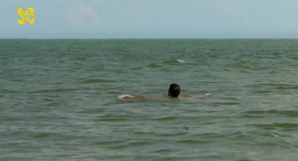 Elias boia no mar, no plano final